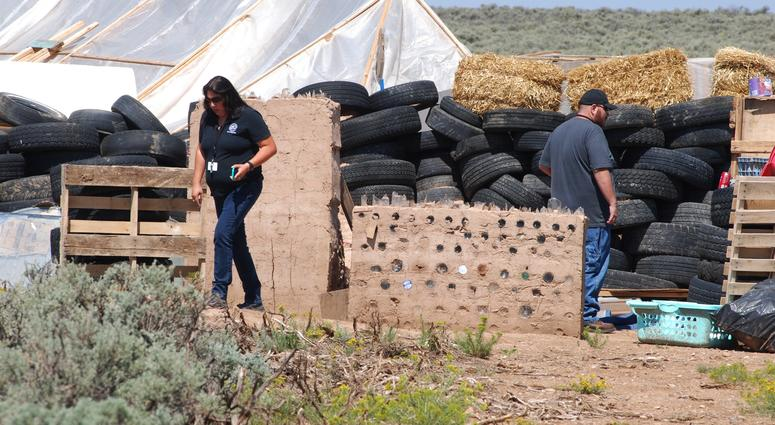 Taos County Planning Department officials Rachel Romero, left, and Eric Montoya survey property conditions at a disheveled living compound at Amalia, N.M., on Tuesday, Aug. 7, 2018.