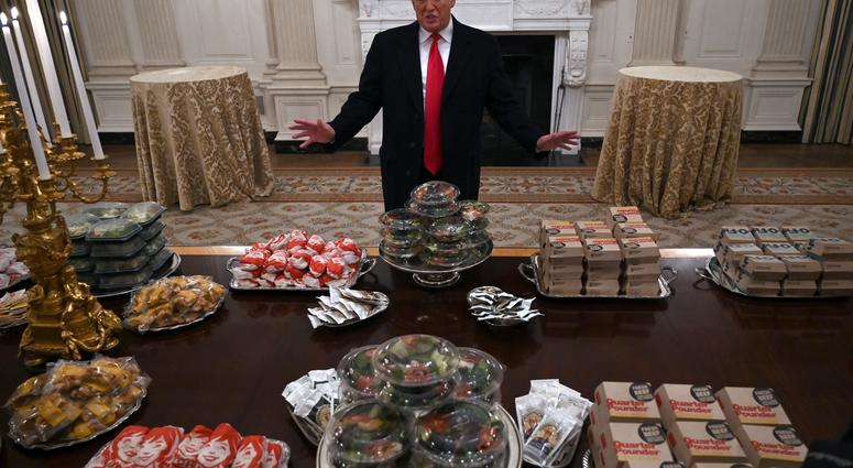 President Donald Trump talks to the media about the table full of fast food in the State Dining Room of the White House