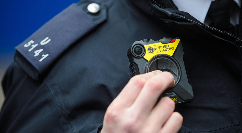 PC Green demonstrates switching on a body-worn camera (BWC) at Brixton Police Station on January 25, 2017 in London, England.