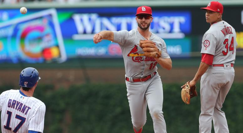 St. Louis Cardinals shortstop Paul DeJong (12) forces out Chicago Cubs third baseman Kris Bryant (17) on the front end of a double play with second baseman Yairo Munoz (34) watching on during the fifth inning at Wrigley Field.