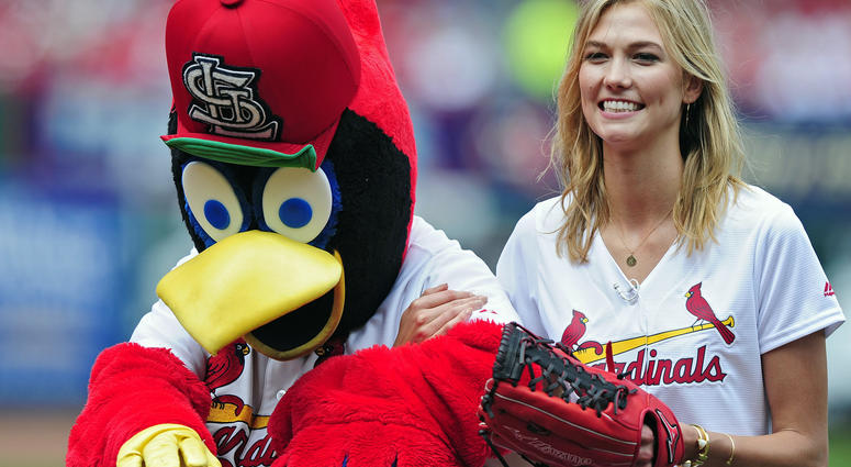 St. Louis native model and entrepreneur Karlie Kloss is escorted off the field by mascot Fredbird after throwing out a first pitch before a game against the Arizona Diamondbacks at Busch Stadium.
