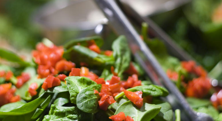 Fresh spinach salad with red peppers.