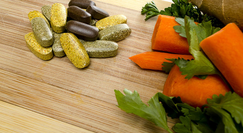 Vitamins on a cutting board with vegetables