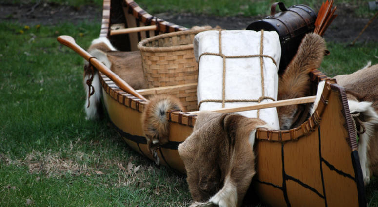 Indian canoe filled with fur pelts and handmade basket for trade.