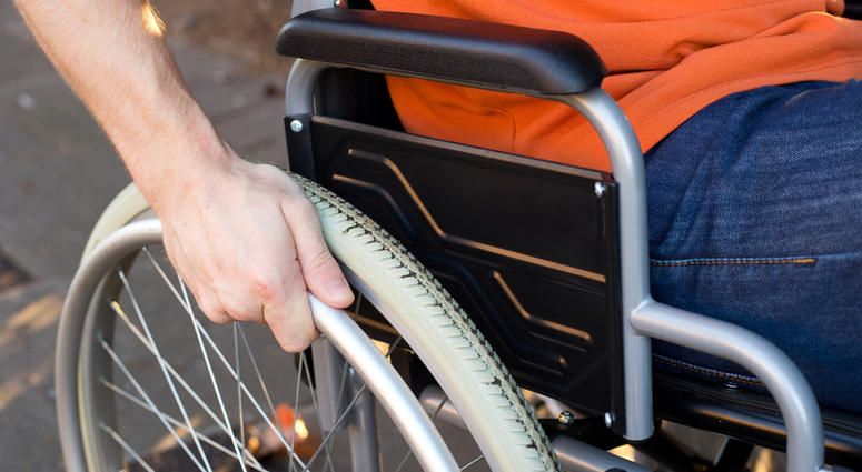 A young wheelchair user with his hand on the wheel