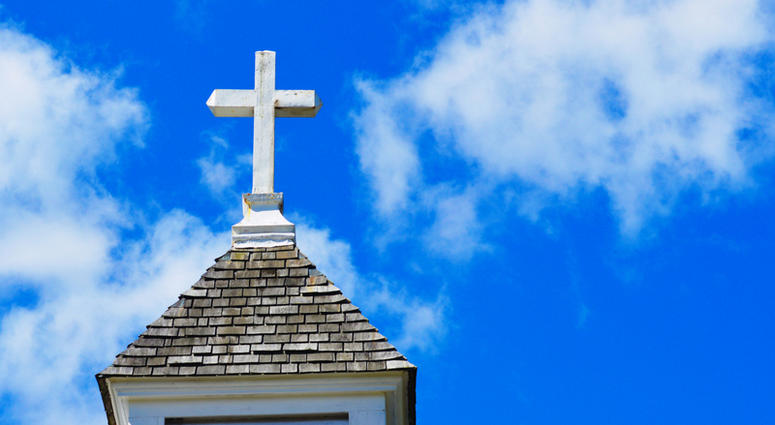 A white church steeple with cross