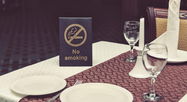 No smoking sigh on table with glasses, napkin and plates in restaurant.