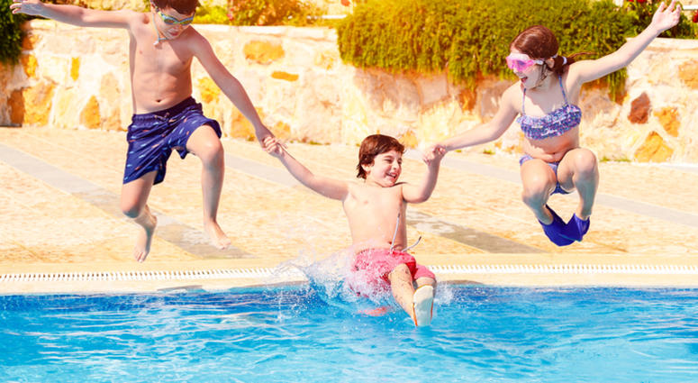 Happy children in the pool, three active friends with pleasure jumping tho the water, enjoying summer holidays on the beach resort