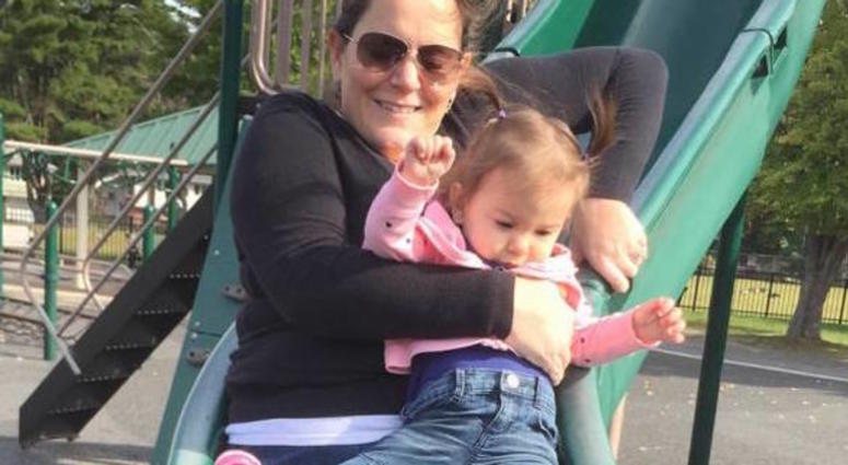 The photo shows the child riding down a slide in her mother's lap.
