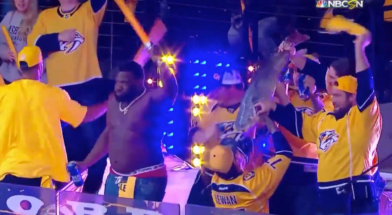 Tennessee Titans player chugs a beer from a catfish at Predators playoff game.