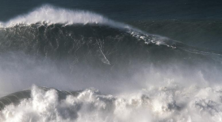Brazilian surfer Rodrigo Koxa rides what has been judged the biggest wave ever surfed, at the Praia do Norte, or North beach, in Nazare, Portugal.