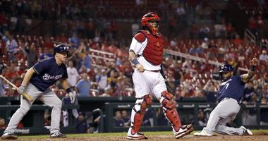Milwaukee Brewers' Eric Thames, right, scores past St. Louis Cardinals catcher Yadier Molina