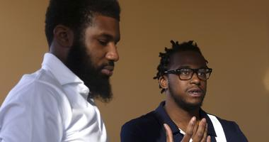 In this Wednesday, April 18, 2018 photo, Rashon Nelson, left, listens as and Donte Robinson, right, addresses a reporter's question during an interview with The Associated Press in Philadelphia. Their arrests at a local Starbucks quickly became a viral vi