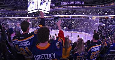 Fans turn on hold up their cell phone flash lights during Hockey Fights Cancer ceremony