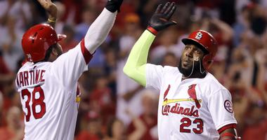 St. Louis Cardinals' Marcell Ozuna (23) is congratulated by teammate Jose Martinez