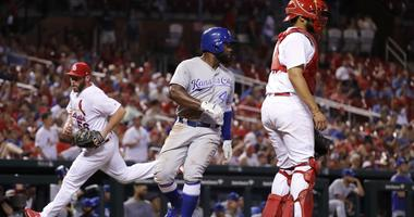 Kansas City Royals' Abraham Almonte, center, looks back as he scores a run, between St. Louis Cardinals relief pitcher Greg Holland and catcher Francisco Pena