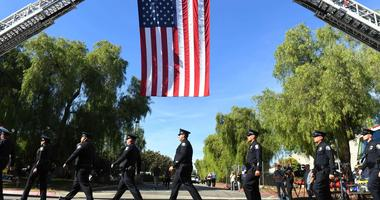 Police officers walk under a large American flag on their way to the funeral