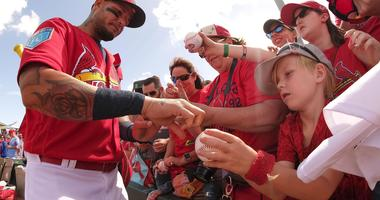 Yadier Molina sign autographs for fans at Roger Dean Stadium.
