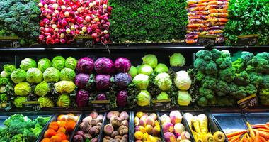 Fresh produce of carrots, beets, celery, bok choy, spinach, kale, lemon grass, radios, broccoli, cilantro, rutabaga, turnip, parsnip and more line the shelves of grocery store.