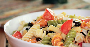 A corkscrew pasta salad with black beans and tomatoes in a white serving bowl.