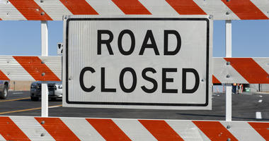 Worn Road Closed Sign in front of street being repaired