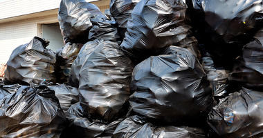A pile of black garbage bags outside transfer station