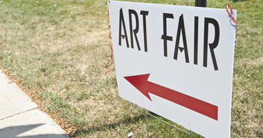 A sign that says ART FAIR with a red arrow pointing left.