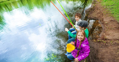 View from up of kids sitting together near the pond holding colorful fishing tackles in beautiful forest landscape