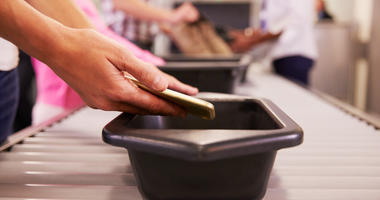 Man Puts Mobile Phone Into Tray For Airport Security Check