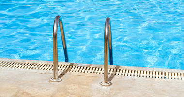 Metal hand railing of staircase to public swimming pool with clear blue water.