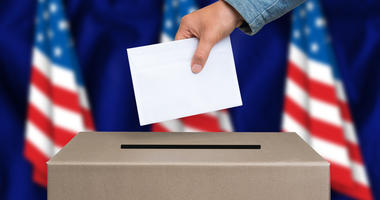 The hand of woman putting her vote in the ballot box. American flags on background.