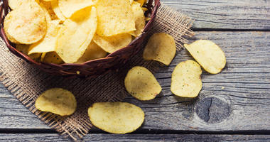 Crispy potato chips in a wicker bowl on old wooden background