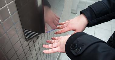 Man drys his hands in a public bathroom.