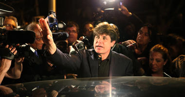 Former Illinois Gov. Rod Blagojevich waves to the crowd in front of his home as he leaves for prison on March 15, 2012, in Chicago.