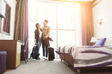 Young happy couple arrived to hotel room on honeymoon
