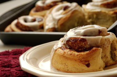 Cinnamon roll on a plate with a pan full of more cinnamon rolls