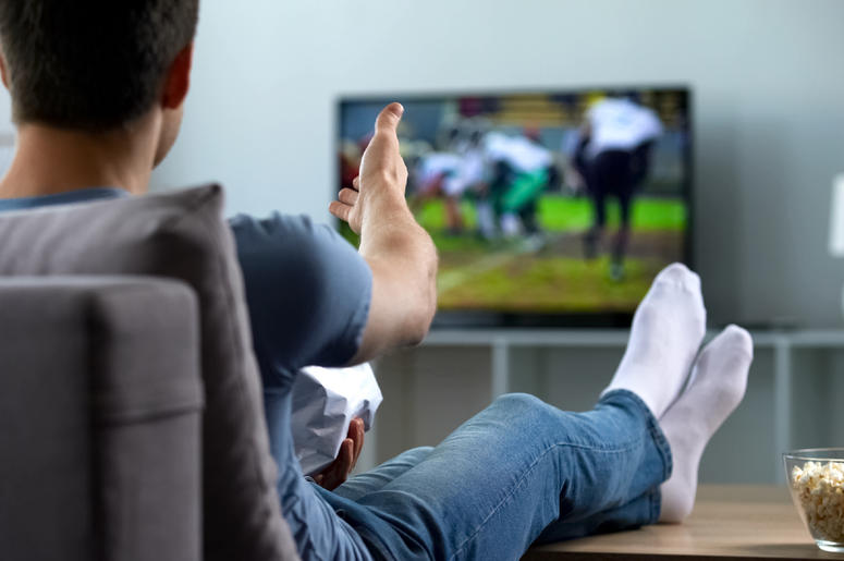 Fan watching football on his couch.