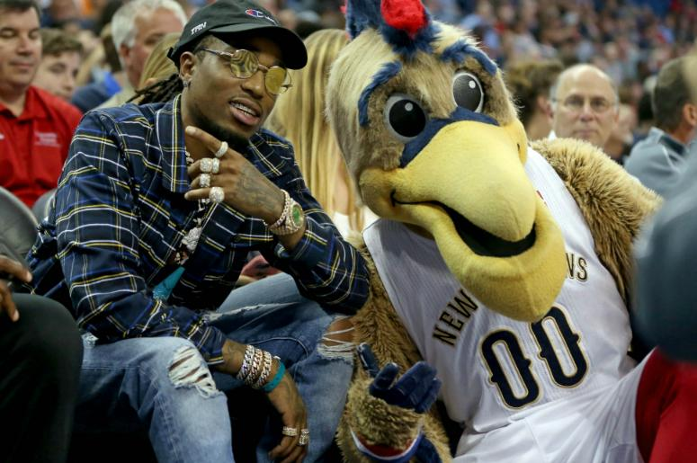 Quavo from the hip-hop group Migos poses with the New Orleans Pelicans mascot in the second half of the game against the Toronto Raptors at the Smoothie King Center.