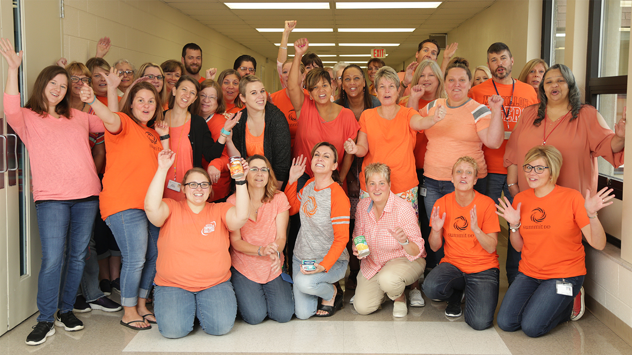 Summit DD Group Photo wearing orange t-shirts
