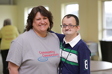 Day program staff member posing with Brad who attends the program