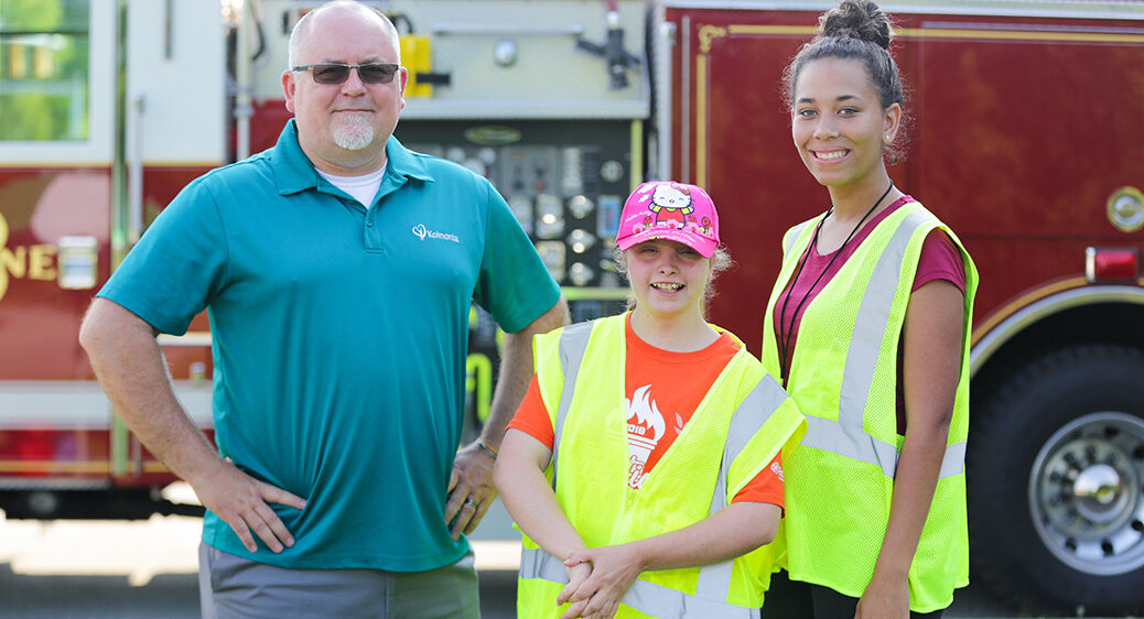 3 people from the Summer Youth Work Experience program smiling by a Stow fire truck