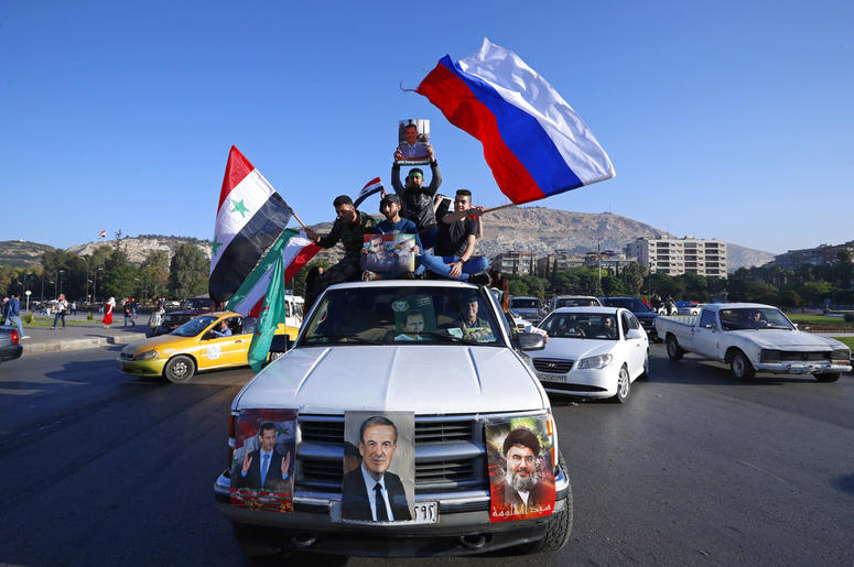 Syrian government supporters wave Syrian, Iranian and Russian flags as they chant slogans against U.S. President Trump during demonstrations following a wave of U.S., British and French military strikes to punish President Bashar Assad.