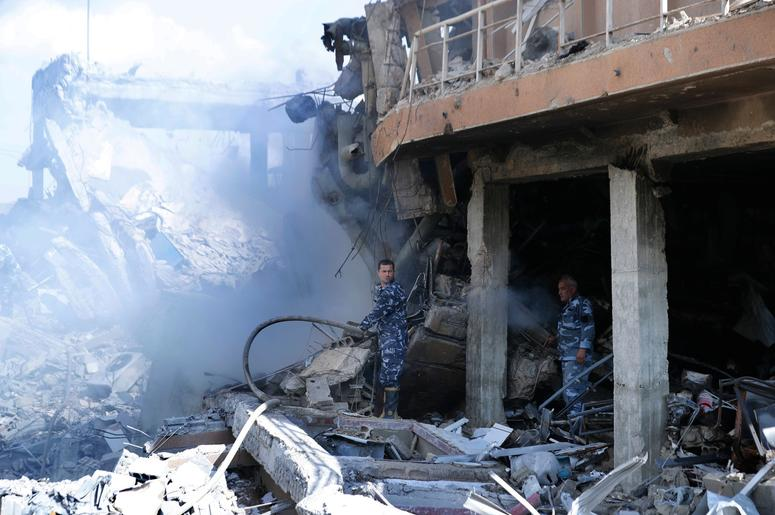 Firefighters extinguish smoke that rises from the damage of the Syrian Scientific Research Center which was attacked by U.S., British and French military strikes to punish President Bashar Assad for suspected chemical attack against civilians, in Barzeh.