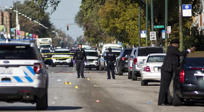 In this Monday, Oct. 22, 2018 photo, Chicago Police investigate following a shooting after a funeral service in Chicago. Police scrambled Tuesday to ward off retaliatory attacks by street gangs after a Chicago rapper known for taunting rivals on social me