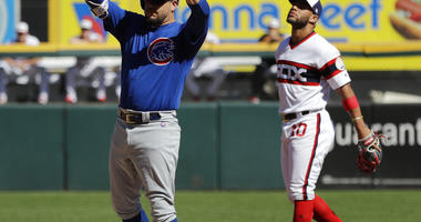 Chicago Cubs' Kyle Schwarber, left, celebrates after hitting a one-run double as Chicago White Sox second baseman Yoan Moncada reacts during the third inning of a baseball game, Sunday, Sept. 23, 2018, in Chicago. (AP Photo/Nam Y. Huh)
