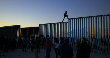 In this Nov. 14, 2018 picture, a man from Honduras walks along the top of the border structure separating Mexico and the United States, in Tijuana, Mexico. With about 3,000 Central American migrants having reached the Mexican border across from California