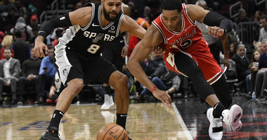 San Antonio Spurs guard Patty Mills (8) and Chicago Bulls guard Shaquille Harrison (3) go for the ball during the first half of an NBA basketball game Monday, Nov. 26, 2018, in Chicago.