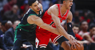 Chicago Bulls forward Chandler Hutchison, right, tries to keep the ball away from Boston Celtics forward Jayson Tatum, left, during the second half of an NBA basketball game, Saturday, Dec. 8, 2018, in Chicago. (AP Photo/Kamil Krzaczynski)