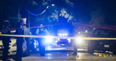 Police investigate the scene where multiple people were shot Sunday morning in the 1600 block of South Avers