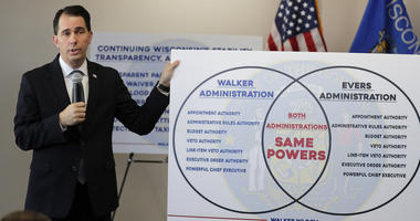 Walker signs last-minute limits on Democratic powers in Wisconsin